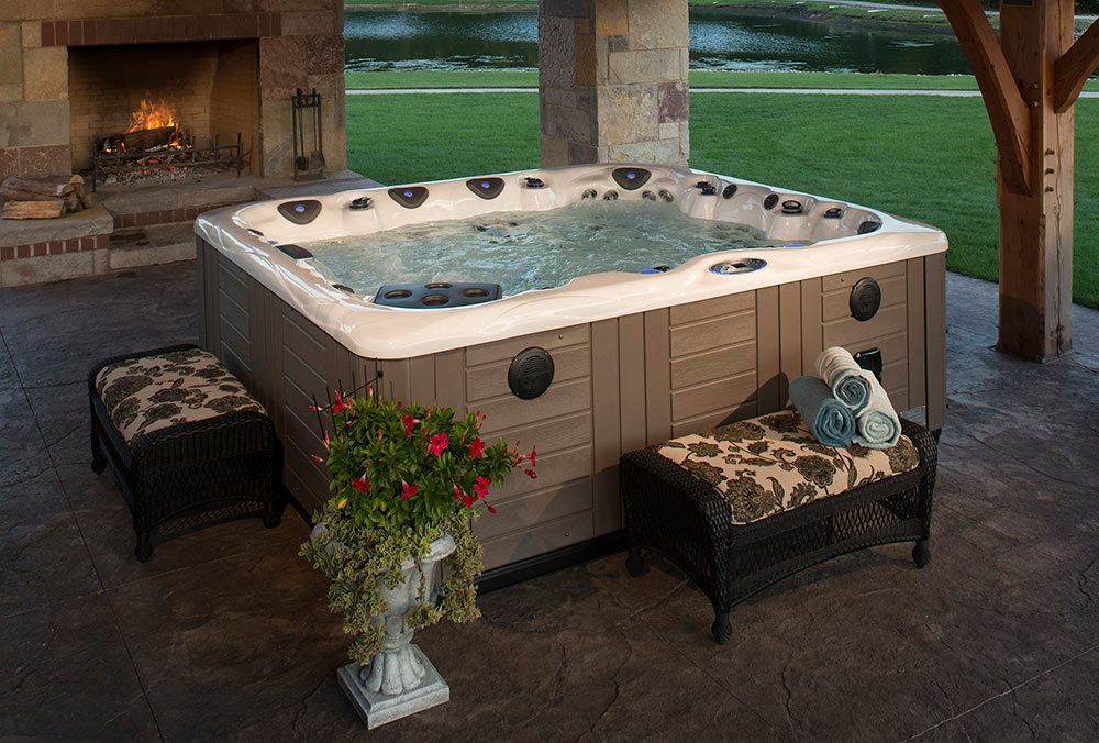 Hot tub installed on covered patio with fireplace