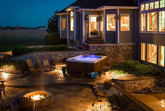 Hot tub on paver patio with firepit in evening